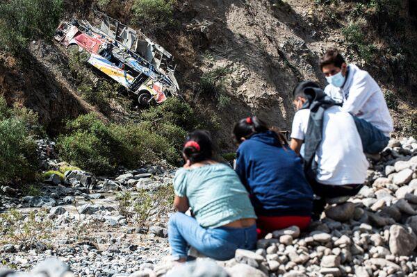 Lidé sedí u místa havárie autobusu v Peru - Sputnik Česká republika