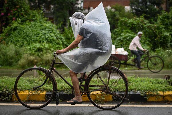 Cyklista zakrytý igelitovým sáčkem během bouřky v indickém Farídábádu - Sputnik Česká republika