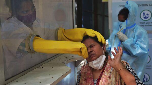 Медицинский работник проводит тест в Индии - Sputnik Česká republika
