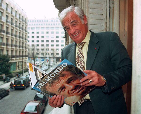 Herec Jean-Paul Belmondo pózuje s knihou o sobě v roce 1996 - Sputnik Česká republika