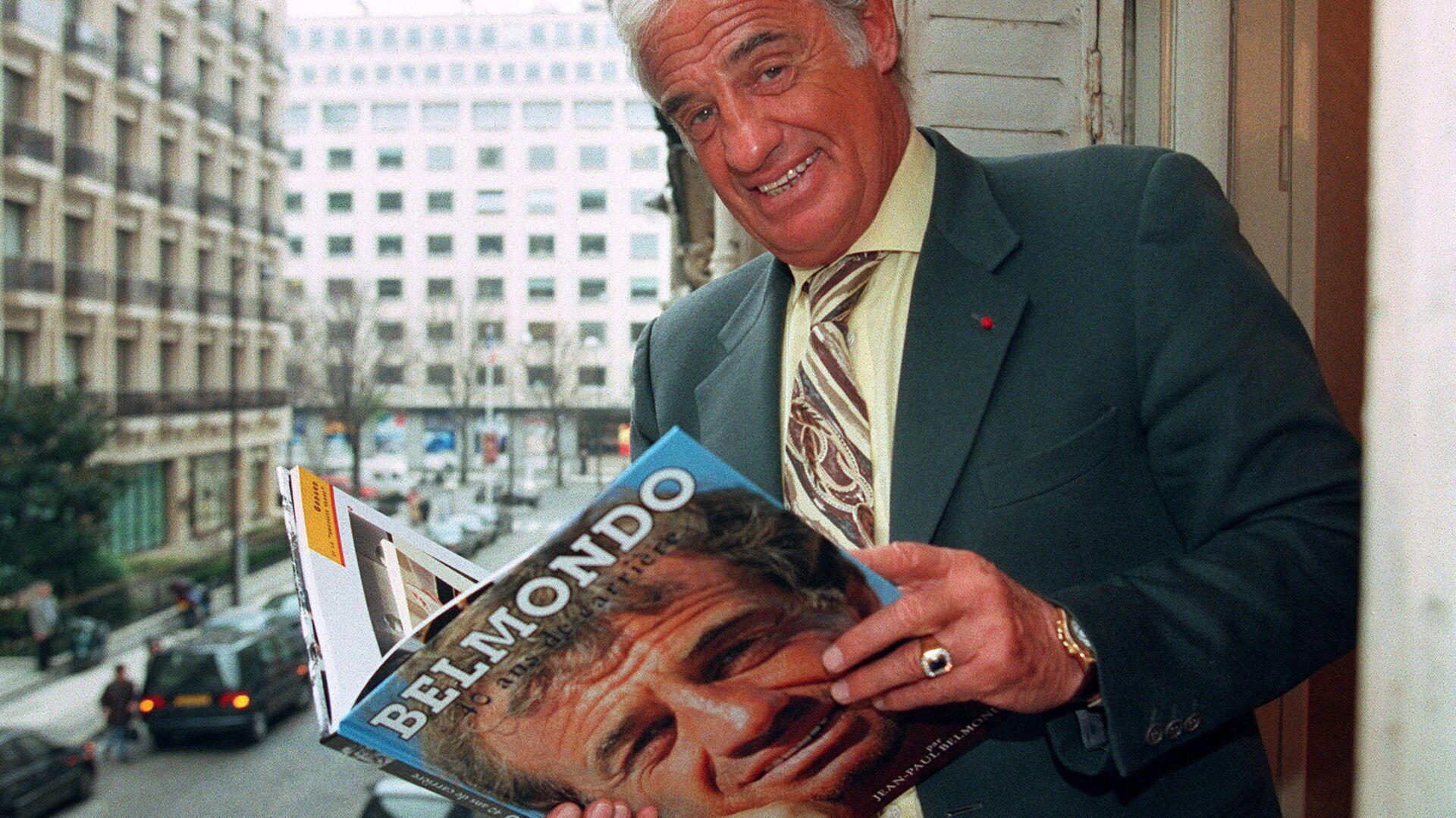 Herec Jean-Paul Belmondo pózuje s knihou o sobě v roce 1996 - Sputnik Česká republika, 1920, 07.09.2021