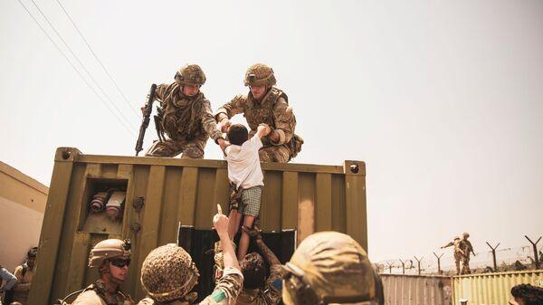 Британские, турецкие и американские солдаты с детьми во время эвакуации в аэропорту Кабула  - Sputnik Česká republika