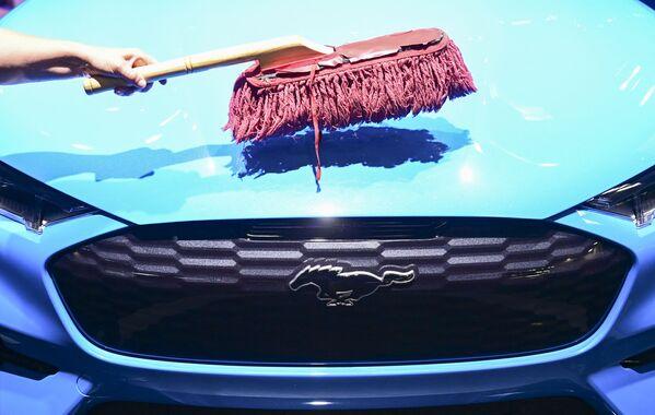 Pracovník čistí kapotu elektromobilu Ford Mustang Mach-E GT u stánku Ford - Sputnik Česká republika