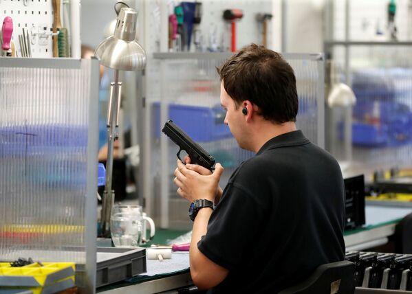 Pracovník zbrojní továrny testuje hotový výrobek.  - Sputnik Česká republika