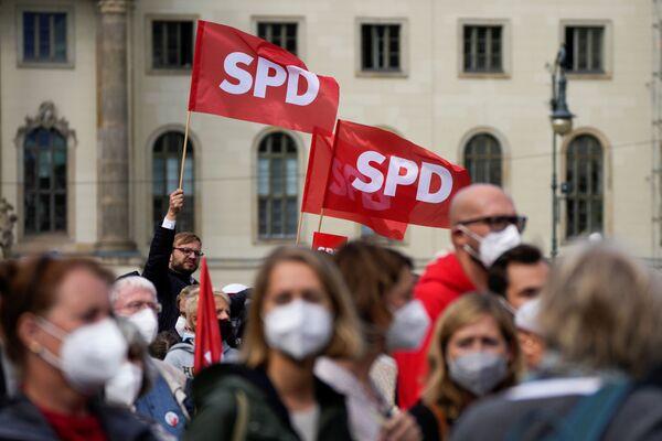 Люди машут флагами Социал-демократической партии Германии во время мероприятия в Берлине - Sputnik Česká republika