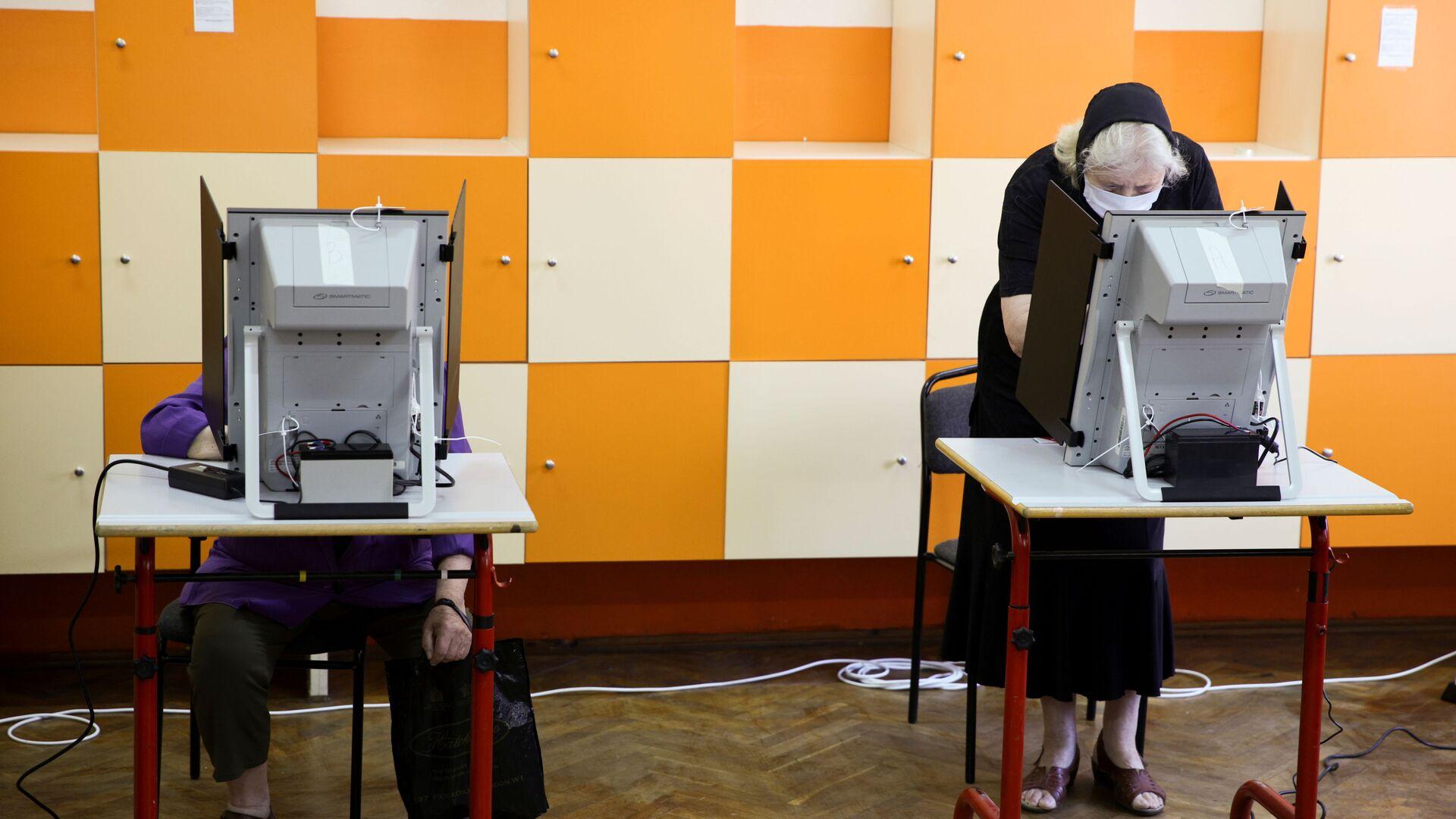 Voliči hlasují v předčasných parlamentních volbách ve volební místnosti v bulharské Sofii - Sputnik Česká republika, 1920, 20.09.2021