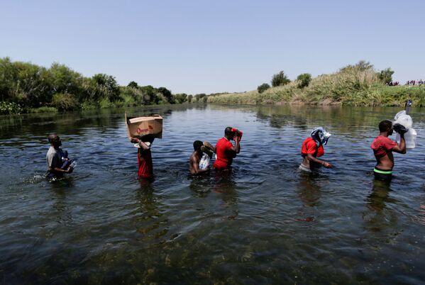 Uprchlíci s doplněnými zásobami se brodí přes řeku Rio Grande, která rozděluje hranici mezi USA a Mexikem. - Sputnik Česká republika