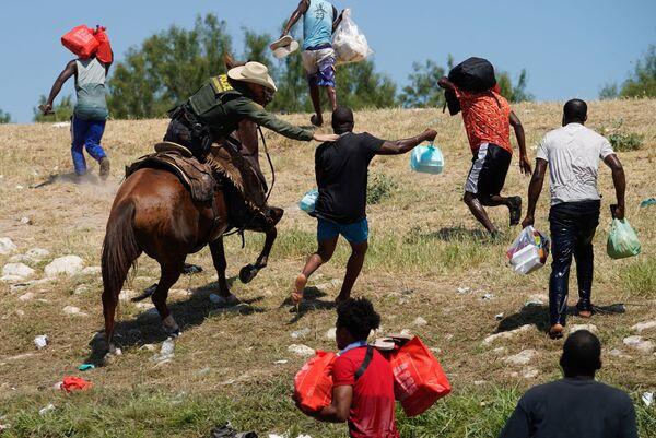 Agent pohraniční stráže na koni se snaží chytit nelegálního migranta. - Sputnik Česká republika