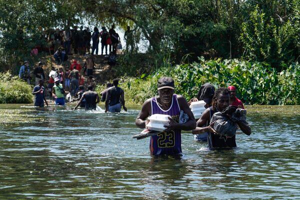 Poté, co si nakoupili v Mexiku, migranti překračují brod přes řeku Rio Grande na americkou stranu. - Sputnik Česká republika