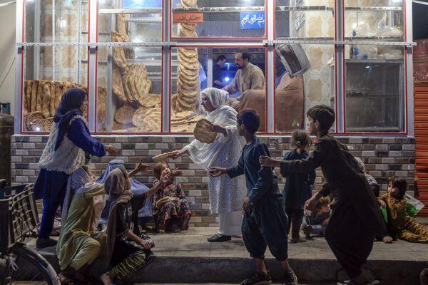Žena rozdává chléb dětem v nouzi před pekárnou v Kábulu - Sputnik Česká republika