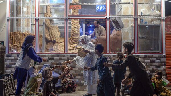 Женщина раздает хлеб нуждающимся детям перед пекарней в Кабуле - Sputnik Česká republika