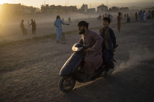 Afghánci jezdí na skútru v parku Chaman-e-Khozari v Kábulu - Sputnik Česká republika