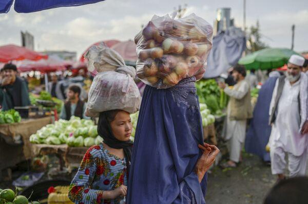 Žena v burce nese na hlavě pytel cibule na tržišti v Kábulu - Sputnik Česká republika