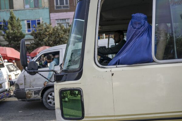 Žena v burce jede autobusem přes Kábul - Sputnik Česká republika