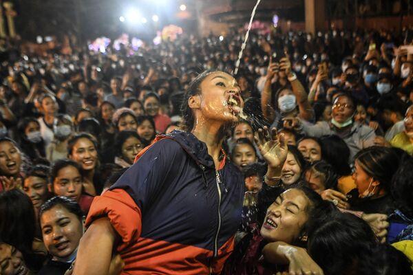 Dívka pije víno ze sochy Shvet Bhairava během festivalu Indra Jatra v Káthmándú - Sputnik Česká republika