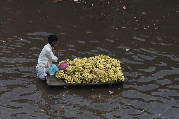 Prodejce ovoce s vozíkem na zaplavené ulici v Láhauru, Pákistán - Sputnik Česká republika