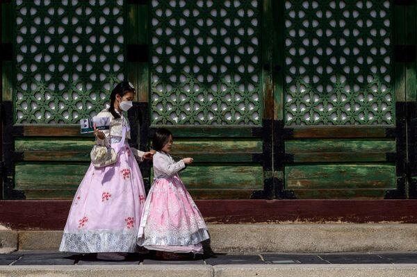 Návštěvníci v tradičních šatech v paláci Gyeongbokgung v Soulu - Sputnik Česká republika