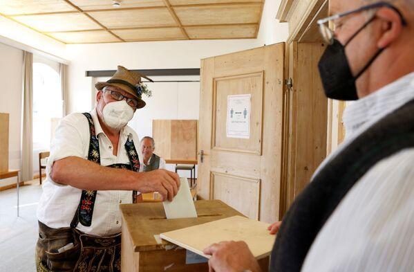 Muž v tradičním bavorském kostýmu během voleb. - Sputnik Česká republika