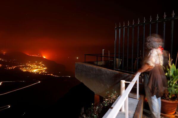 Žena pozoruje erupci sopky. - Sputnik Česká republika