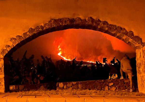 Muž pozoruje chrlení lávy a stoupající kouř. - Sputnik Česká republika