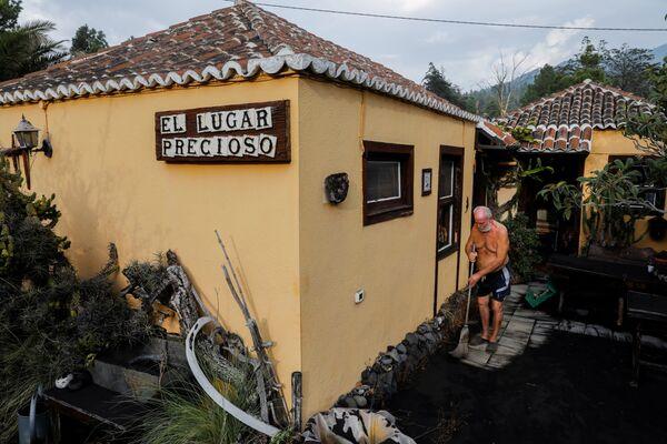 Muž uklízí popel vedle svého domova. - Sputnik Česká republika