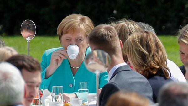 Německá kancléřka Angela Merkelová pije kávu na akci v Berlíně - Sputnik Česká republika