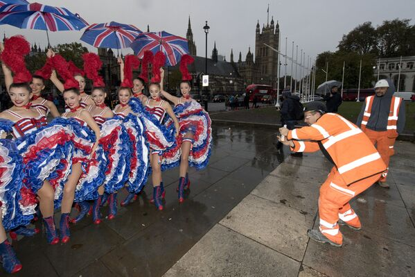 Рабочие фотографируют танцовщиц из парижского кабаре Мулен Руж в Лондоне  - Sputnik Česká republika