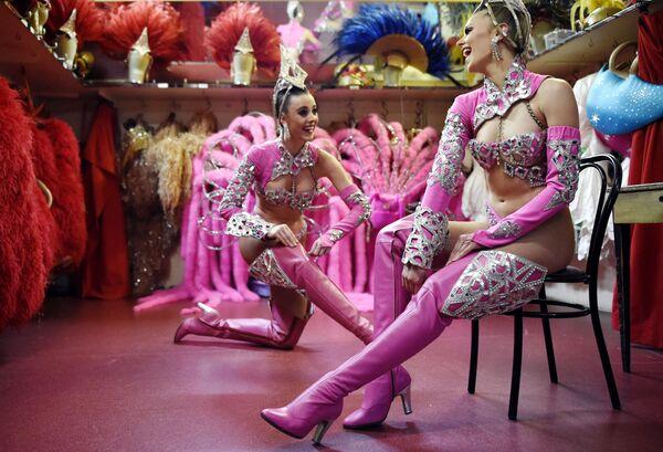 Kabaretní tanečníci Moulin Rouge si před vystoupením dne 22. dubna 2014 v Paříži rovnají boty. Od roku 1945 se Maison Clairvoy specializuje na výrobu luxusní obuvi a v roce 1960 zahájila spolupráci se slavným Moulin Rouge na vytvoření bot a obuvi pro francouzské tanečnice kankánu - Sputnik Česká republika