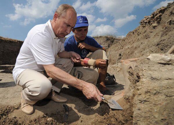 10. srpna 2011. Ruský premiér Vladimir Putin (vlevo) při návštěvě tábora archeologů, kteří vykopávají jedinečné starověké řecké město Fanagoria, čistí starodávnou amforu - Sputnik Česká republika