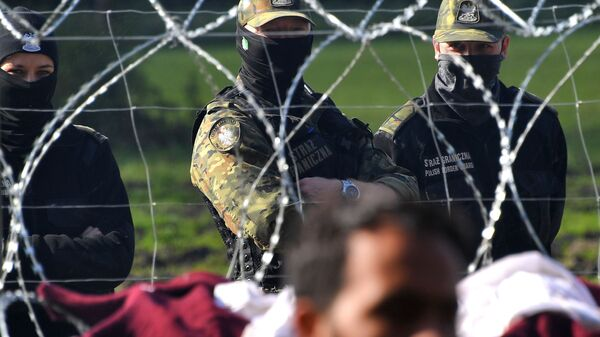 Польские пограничники наблюдают за лагерем беженцев из Афганистана на белорусско-польской границе возле деревни Уснар-Дольное - Sputnik Česká republika