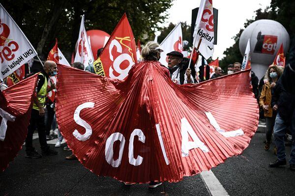 Žena s transparentem během demonstrací francouzských odborů, které vystupují za lepší pracovní podmínky, a protestují proti reformám důchodů a podpory nezaměstnaných. Bordeaux, 5. října 2021. - Sputnik Česká republika