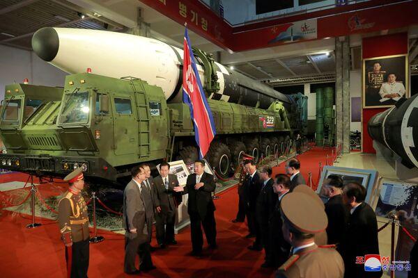 Severokorejský vůdce Kim Čong-un během svého proslovu vedle vystavených vojenských zbraní a vozů. Mezi nimi jsou například mezikontinentální balistické rakety. - Sputnik Česká republika