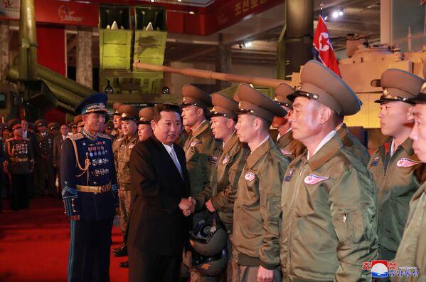 Severokorejský vůdce Kim Čong-un zdraví příslušníky vojenské služby během výstavy. - Sputnik Česká republika