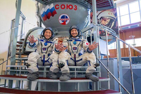 Júsaku Maezawa a Jozo Hirano pózují na pozadí simulátoru kosmické lodi Sojuz během výcviku před expedicí na Mezinárodní vesmírnou stanici. - Sputnik Česká republika