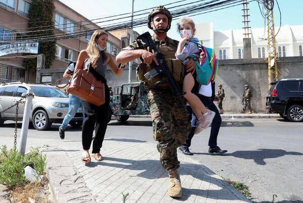 Armádní voják nese školáka, zatímco civilisté začali utíkat před střelbou, která vypukla na místě poblíž protestu. - Sputnik Česká republika