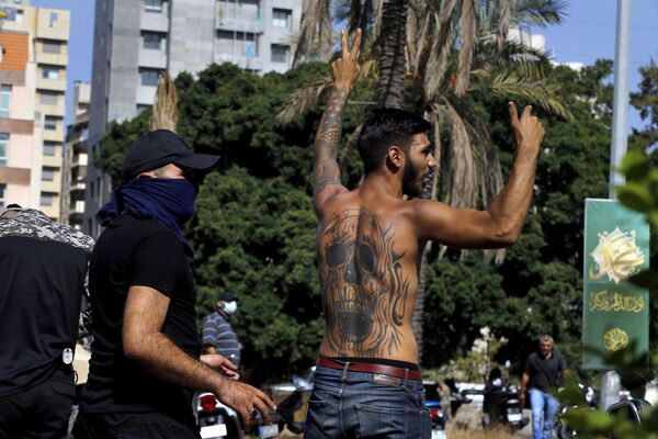 Stoupenec šíitského hnutí Hizballáh ukazuje znamení vítězství během ozbrojených střetů, které propukly během protestu v libanonském hlavním městě Bejrútu. - Sputnik Česká republika