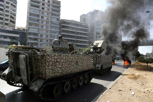 Libanonští vojáci hlídkují ve svém obrněném vozidle, zatímco stoupenci skupin šíitského Hizballáhu a Amalu pálí během protestu kontejnery na odpadky za účelem zablokování silnice. - Sputnik Česká republika