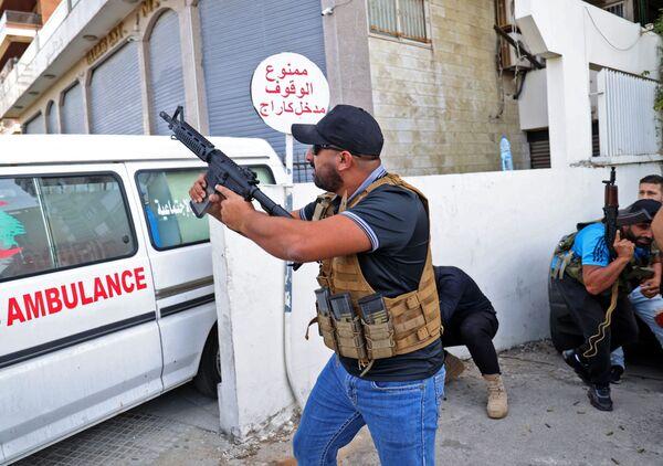 Bojovník z hnutí Amal míří zbraní během střetů v oblasti Tayouneh, na jižním předměstí hlavního města Bejrút. - Sputnik Česká republika