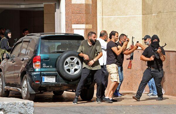 Bojovníci ze šíitského hnutí Hizballáh a Amal během střetů v oblasti Tayouneh na jižním předměstí Bejrútu. - Sputnik Česká republika