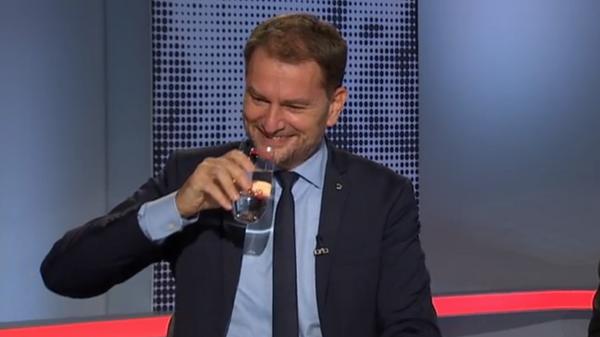 Скриншот видео. Министр финансов Словакии Igor Matovič смеётся и держит стакан с водой  - Sputnik Česká republika