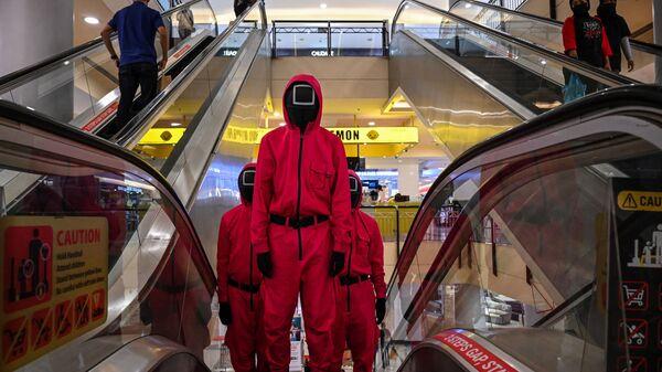 Косплееры в костюмах персонажей из сериала Netflix Игра в кальмара на эскалаторе в торговом центре Куала-Лумпура, Малайзия - Sputnik Česká republika