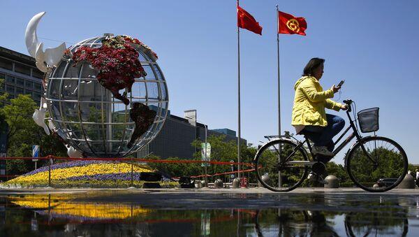 Žena jede na kole před budovou banky v Pekingu - Sputnik Česká republika