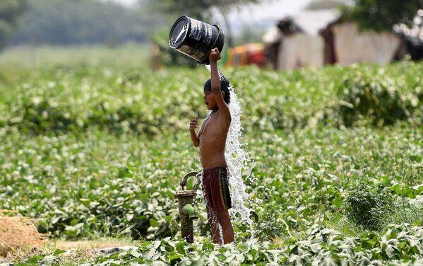 Chlapec se polévá vodou v hlavním městě Indie Novém Dillí. - Sputnik Česká republika
