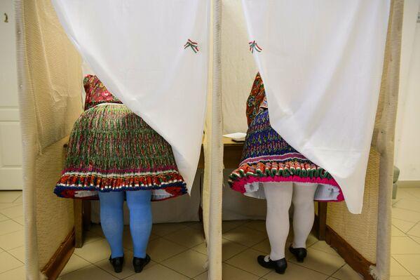 Ženy v národním kroji hlasují ve volbách do Evropského parlamentu v maďarském městě Buják. - Sputnik Česká republika