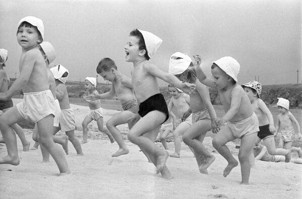 Chovanci mateřské školky běží po pláži v Dněpru, Ukrajinská SSR, 1966 - Sputnik Česká republika