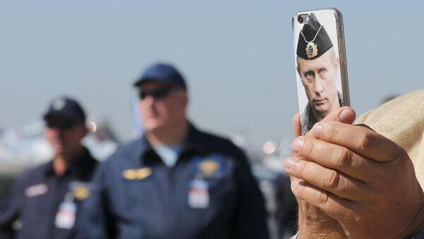 Návštěvník MAKS 2015 fotografuje telefonem s obrazem ruského prezidenta Vladimira Putina. - Sputnik Česká republika