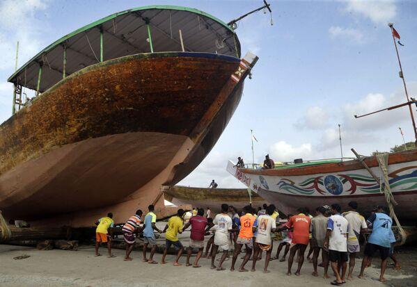 Indičtí rybáři přepravují loď na suchou půdu před začátkem monzunového období dešťů. - Sputnik Česká republika