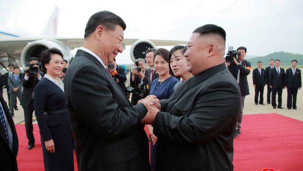Severokorejský vůdce Kim Čong-un vítá čínského vedoucího představitele Si Ťin-pchinga na mezinárodním letišti v Pchjongjangu - Sputnik Česká republika