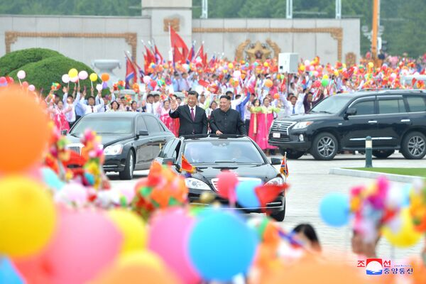 Vůdce KLDR Kim Čong-un a prezident Číny Si Ťin-pching jedou Pchjongjangem. - Sputnik Česká republika