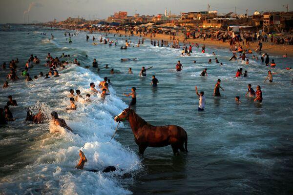 Lidé se koupají v Středozemním moři v severní části Pásma Gaza. - Sputnik Česká republika